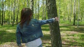 A jovem mulher vem até a árvore põe a mão sobre ela, gerencie ao redor sua cabeça e sorri olhando a câmera filme