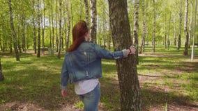 A jovem mulher vem até a árvore põe a mão sobre ela, gerencie ao redor sua cabeça e sorri olhando a câmera vídeos de arquivo