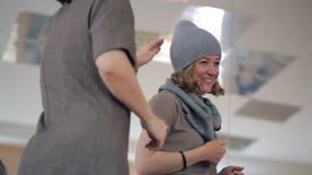 A jovem mulher veste um chapéu cinzento em sua cabeça e o riso com amigos filme