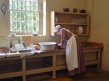 Jovem mulher vestida como pratos de lavagem da empregada doméstica da cozinha de Victoria no dissipador foto de stock