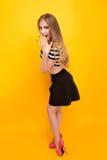 Jovem mulher vestida do estilo ocasional que está contra o amarelo fotografia de stock