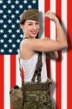 Jovem mulher vestida na mostra ww2 uniforme militar seu bíceps, ame imagem de stock royalty free