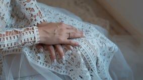 A jovem mulher vestida no vestido branco está sentando-se na sala dentro vídeos de arquivo