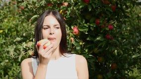 A jovem mulher vestiu-se em um vestido branco que gira em torno e que levanta na câmera na frente do sol na Apple-árvore video estoque
