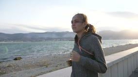 A jovem mulher vestiu-se no hoodie que movimenta-se na cidade na frente marítima filme