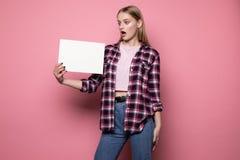 Jovem mulher virada chocada na roupa ocasional, guardando a placa vazia branca para seu texto imagens de stock