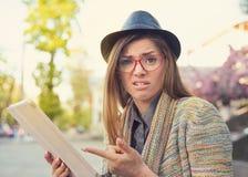 Jovem mulher virada com a tabuleta que olha a câmera fotos de stock