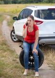A jovem mulher virada obteve seu pneu de carro puncionado e chamando o auto serviço para a ajuda imagem de stock