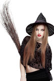 Jovem mulher vistoso no traje da bruxa com uma vassoura Fotos de Stock