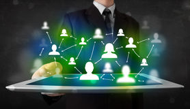 Jovem que apresenta a tabuleta com ícones sociais verdes dos meios Imagem de Stock