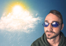 Jovem que olha com os óculos de sol em nuvens e em sol Foto de Stock Royalty Free