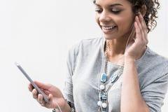 A jovem senhora alegre está estando com o smartphone no ar livre Foto de Stock Royalty Free