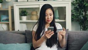 A jovem senhora alegre está fazendo o cartão de banco em linha da terra arrendada do pagamento e está tocando na tela do smartpho vídeos de arquivo