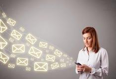 Jovem senhora atrativa que guardara um telefone com ícones da mensagem Fotografia de Stock Royalty Free