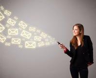 Jovem senhora atrativa que guardara um telefone com ícones da mensagem Imagens de Stock Royalty Free