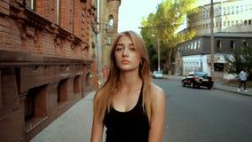 A jovem senhora bonita com cabelo longo olha na câmera video estoque
