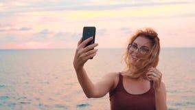 A jovem senhora bonita com cabelo louro do voo na frente do mar e o céu colorido, por do sol em Geórgia, blogger da menina toma o video estoque