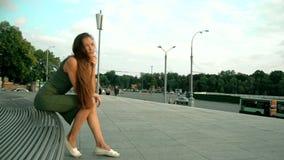 Jovem senhora bonita com o cabelo longo que senta-se em um banco e em uma cabeça de dobra vídeos de arquivo