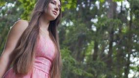 Jovem senhora bonita em caminhadas vermelhas do vestido fora, fêmea moreno na floresta video estoque