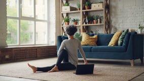 A jovem senhora bonita está aprendendo a ioga das lições em linha que sentam-se no assoalho que olha a tela do portátil e que pra vídeos de arquivo