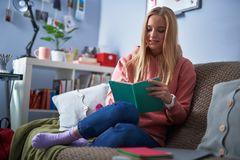 Jovem senhora bonita na escrita cor-de-rosa do hoodie no caderno foto de stock