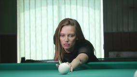 A jovem senhora bonita nova que aponta tomar a sinuca disparou ao inclinar-se sobre a tabela em um clube vídeos de arquivo