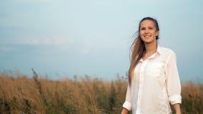 Jovem senhora bonita que anda em campos de trigo durante o por do sol vídeos de arquivo