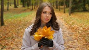Jovem senhora bonita que espera alguém no parque do outono que plaing com sorriso do ramalhete do mapleleaf a alguém vídeos de arquivo
