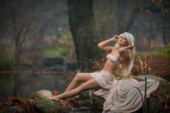Jovem senhora bonita que senta-se perto do rio em madeiras encantados Louro sensual com a roupa branca que levanta provocatively  Foto de Stock Royalty Free