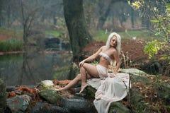 Jovem senhora bonita que senta-se perto do rio em madeiras encantados Louro sensual com a roupa branca que levanta provocatively  Foto de Stock