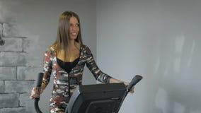 Jovem senhora bonita que usa o instrutor elíptico em um gym em um humor positivo video estoque