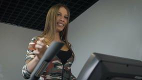 Jovem senhora bonita que usa o instrutor elíptico em um gym em um humor positivo vídeos de arquivo