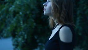 A jovem senhora bonito com cabelo curto vem na noite à cidade filme
