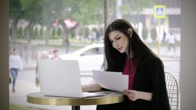 Jovem senhora bonito que trabalha no terno de negócio na moda da cafetaria da tabela Cara bonita com emoção da alegria e do suces filme