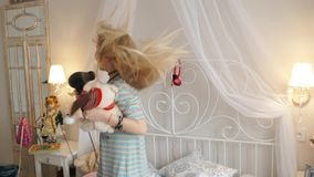 A jovem senhora brincalhão está cantando no secador do sopro, dança e está saltando na cama e está escutando a música vídeos de arquivo