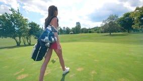 A jovem senhora com acessórios do golfe está andando ao longo do gramado filme