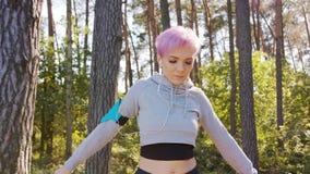 Jovem senhora com o cabelo cor-de-rosa que estica na floresta video estoque