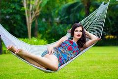 Jovem senhora com o cabelo escuro longo que relaxa na rede no trópico imagem de stock