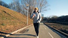 A jovem senhora com um braço robótico está correndo ao longo do parque