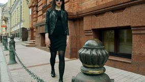 A jovem senhora da beleza no preto anda abaixo da rua video estoque
