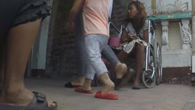 Jovem senhora deficiente na cadeira de rodas com outro que implora video estoque