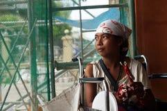 A jovem senhora deficiente na cadeira de rodas vende velas no portal da igreja Fotografia de Stock Royalty Free