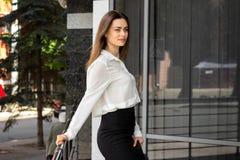 Jovem senhora delgada bonita em uma camisa branca e em uma saia preta imagem de stock