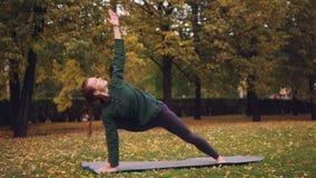 A jovem senhora delgada está fazendo a ioga fora que muda asanas e que aprecia o movimento, o ar fresco e a natureza do outono video estoque