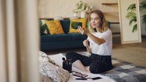 A jovem senhora encantador está pintando as sobrancelhas que põem sobre a composição na manhã que senta-se na cama no apartamento filme