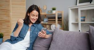 Jovem senhora entusiasmado que comemora o sucesso que olha a tela do smartphone em casa video estoque