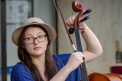 A jovem senhora está ajustando o violoncelo Foto de Stock