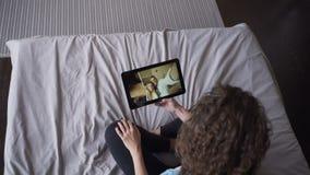A jovem senhora está falando aos pares bonitos em linha com a tabuleta que olha a tela e que fala o assento na cama em casa video estoque