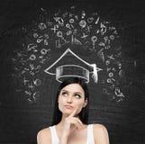A jovem senhora está pensando sobre o estudo na universidade Os ícones educacionais são tirados na placa de giz preta Fotos de Stock Royalty Free