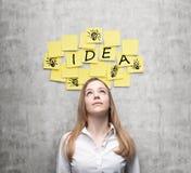 A jovem senhora está procurando ideias novas do negócio As etiquetas amarelas com a palavra 'ideia' e esboços' de ampolas 'são h Fotografia de Stock Royalty Free